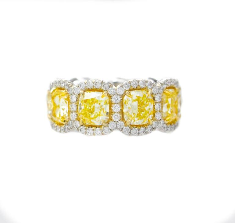 Magnificent Fancy Yellow diamond eternity band, features 9.50 Carats of Fancy Yellow Cushion Cut Diamonds, surrounded by 1.50 Carats of white round brilliant cut diamonds. Each stone is approximately 1.00 carats, cushion cut. Beautiful vibrant