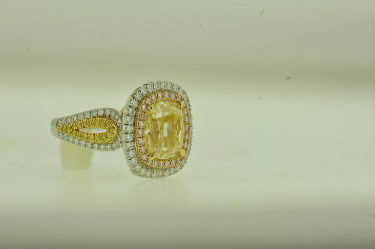 This one of a kind diamond ring, designed by Diana M. Jewels combines three natural colored diamonds, Fancy Pink, Fancy Yellow and White diamonds.  The center stone is 5.02 Carats Fancy Yellow Cushion Cut Diamond, SI1 in Clarity, accompanied by  EGL
