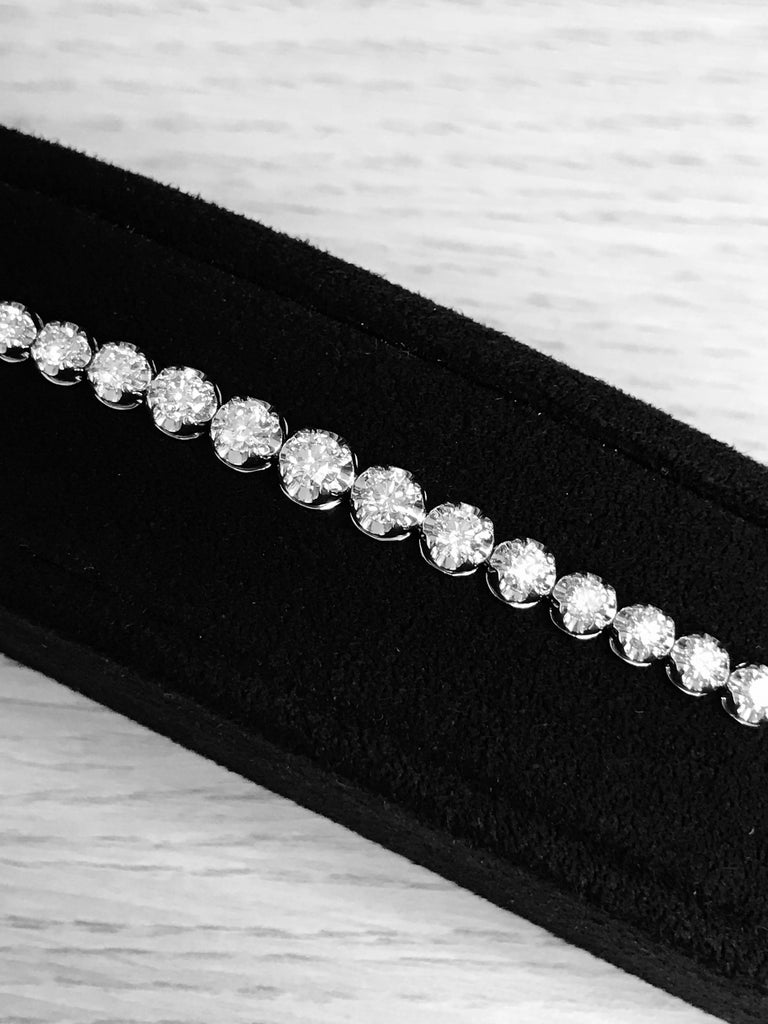 A classic look just for her, this 5 Carat . diamond graduated tennis bracelet is certain to take her breath away. Fashioned in white gold, this eternal design features a brilliant array of sparkling round diamonds arranged so the bigger diamonds are