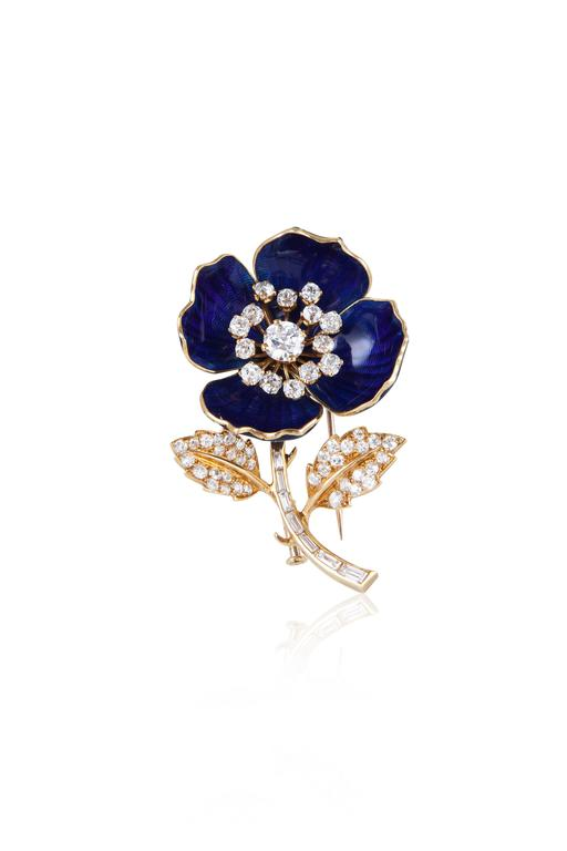 Exceptionally crafted, this pin comes with two separate sets of petals that can be easily swapped depending on one's mood.  The first exhibits a subtly patterned royal blue enamel, while the second is more glamorous with pavé set diamonds.  The