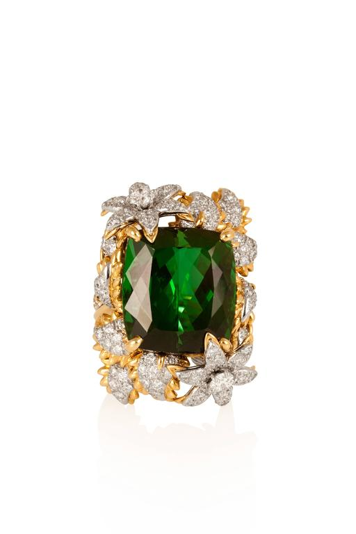 Centered on an exceptional cushion green tourmaline weighing approximately 30 carats, this exuberant ring is decorated with diamond- encrusted flowers and petals, mounted in 18-karat yellow gold and platinum.