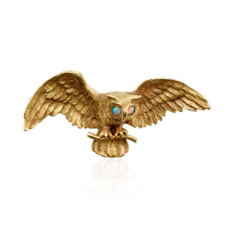 An Art Nouveau 14k yellow gold pin in the form of an owl with outstretched wings, with vibrant opal eyes. Circa 1900.