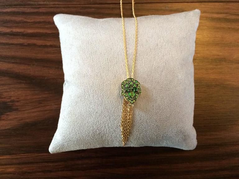 This pendant is handcrafted in London using 18ct yellow gold and is set with 1.20ct of vivid green natural tsavorites. The top of the pendant has a black rhodium finish to contrast with the yellow gold and the tsavorites.   length of pendant