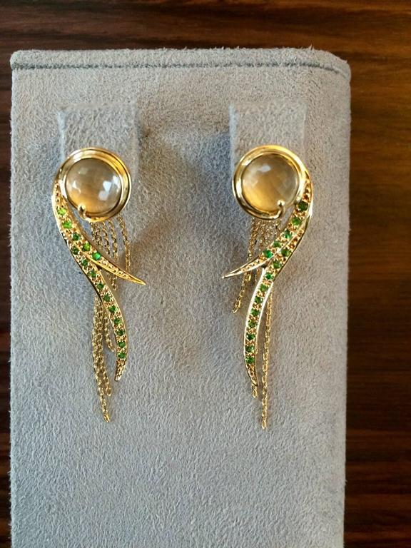 These earrings have been handcrafted in London using 18ct yellow gold and are set with 0.50ct of vivid green natural tsavorites, which are chosen represent brightly coloured magic potions.  The top of the earrings are set with hand cut rock crystal