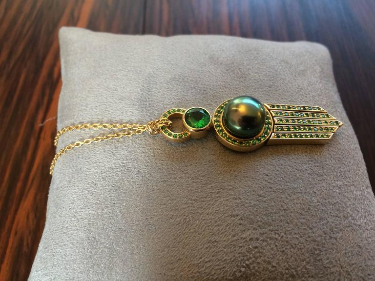 This pendant has been handcrafted in 18ct yellow gold and is a unique one of a kind piece. The large natural tsavorite weighs 0.93ct and the total tsavorite weight is 2.20ct.   The black Tahitian pearl is 11mm in diameter and is an A grade pearl. It