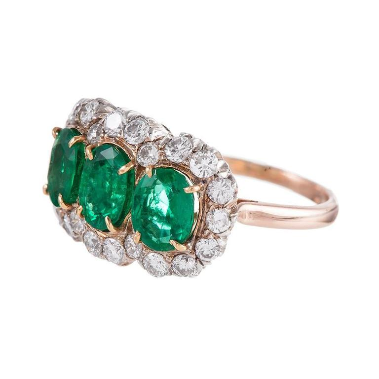 14k white and yellow gold ring set with three oval emeralds and framed by a cluster of white diamonds. Each emerald weighs approximately 1 carat and the twenty-two diamonds weigh 1.00 carat combined. This ring has an impressive presence on the