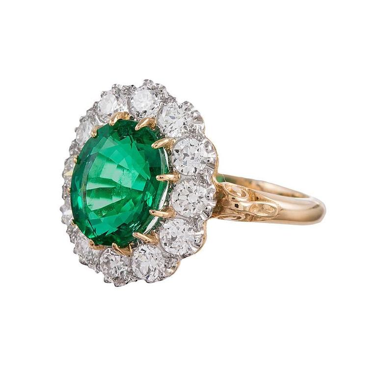 """A classic """"Princess Diana"""" style cluster ring, rendered in platinum and 18 karat yellow gold. The center is set with a 2.73 carat oval brilliant emerald and framed by 1.16 carats of white diamonds. This ring is of a classic vintage design, but of"""