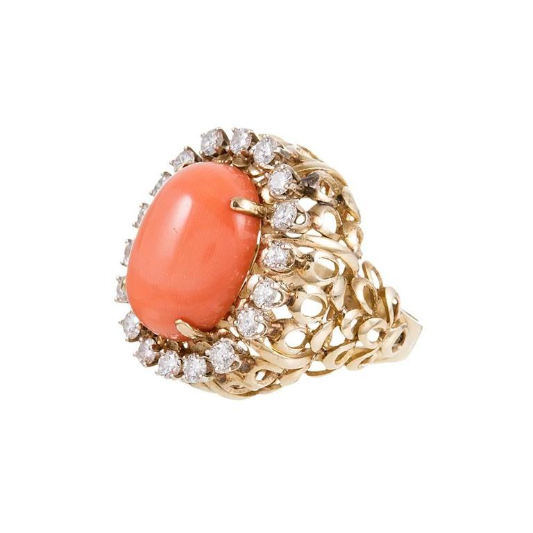 Playful midcentury style abounds with this impressive cocktail ring. The 14k yellow gold mounting is designed as a stacked collection of loops, a repeating pattern that reinforces the midcentury charm. The large coral cabochon is framed in a single