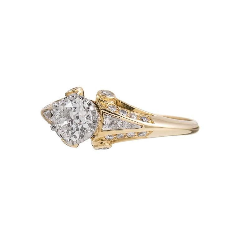 Charming ring made of 18k yellow gold with an 18k white gold crown shaped basket to hold the center stone. The major diamond is accompanied by an EGL diamond grading certificate that describes the diamond as H color and Vs1 clarity. An additional 36