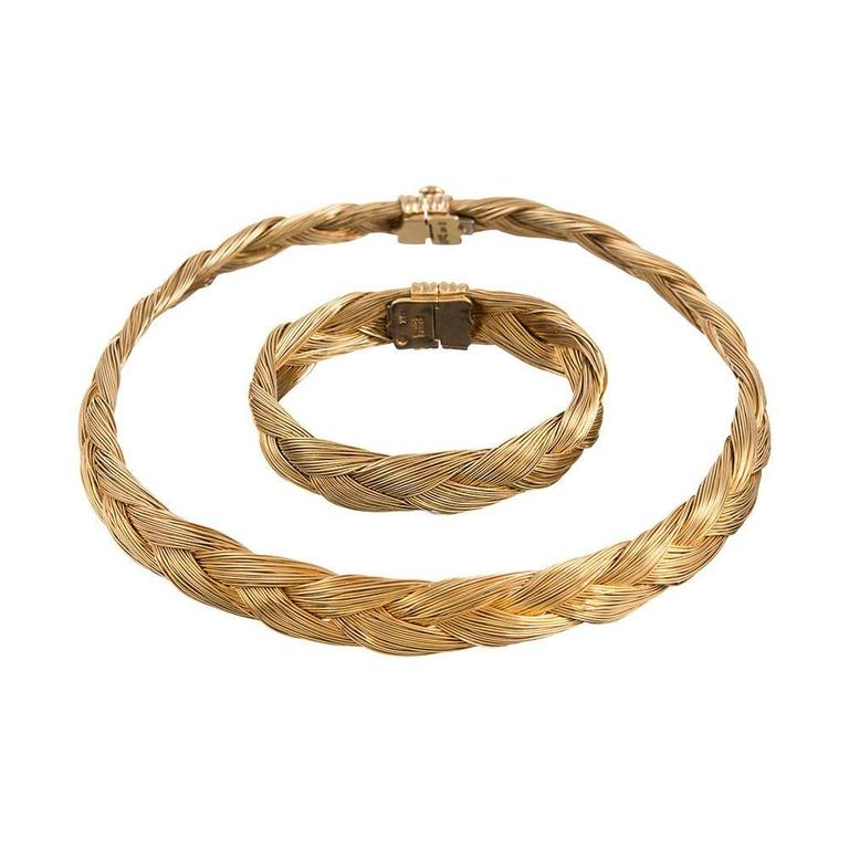 A feminine, substantial, wearable and incredibly chic necklace and bracelet suite, designed as clusters of golden strands fashioned into a single braid. The absence of gemstones allows this suite to be a subtle addition to informal attire, yet it