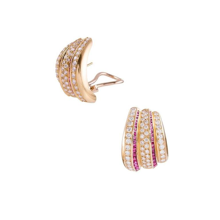 Retro style elements translated into late 20th century design... Intense red rubies and brilliant white diamonds dazzle on stripes of 18k yellow gold and are fashioned into a modified hoop design. 1 ¼ inches tall by 7/8 of an inch wide and finished