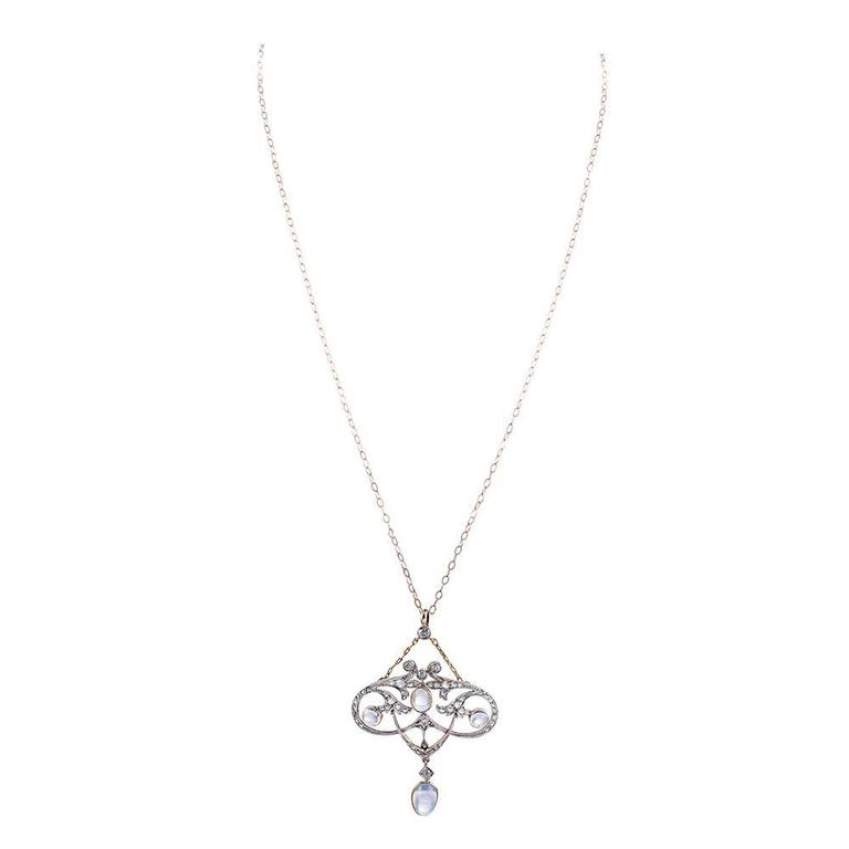 Made of platinum and 18k yellow gold, this ultra-feminine Edwardian creation is decorated with cabochon blue flash moonstones and rose cut diamonds, circa .25 carats in total. The sweeping strokes are fluid and organic. 2.5 by 1.75 inches and
