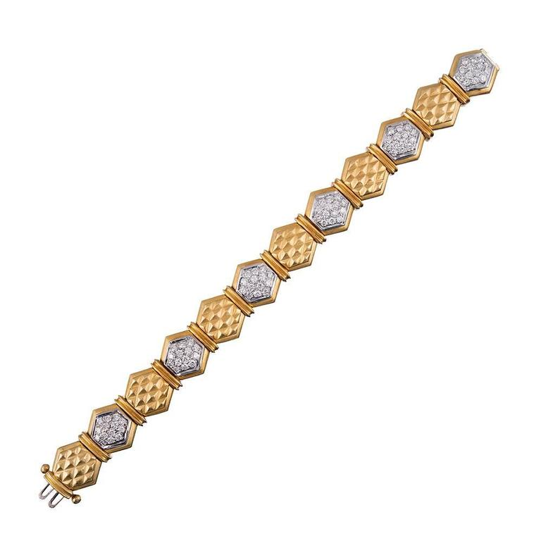 Brushed links of 18k yellow gold textured with a three-dimensional honeycomb pattern alternate with diamond-studded octagons and are separated by double bridges of gold. This bracelet has distinct late 20th century character and is bold enough to