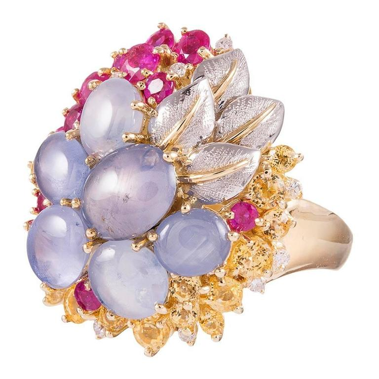 Made of 18 karat yellow gold and decorated with textured platinum leaves, this uncommon array of gemstones forms a bouquet atop your finger. Offering a surprisingly low profile and great comfort on the finger, the mixture of rubies, diamonds, yellow