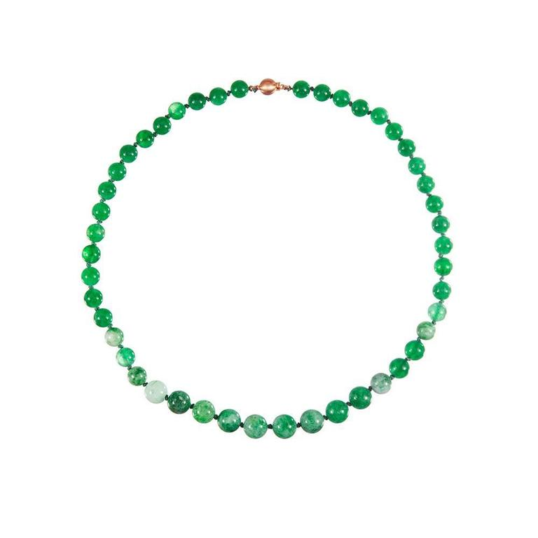 A 19 inch strand comprised of forty seven jadeite beads and finished with an 18k yellow gold ball clasp. The beads measure 10.5 by 8.0 millimeters.