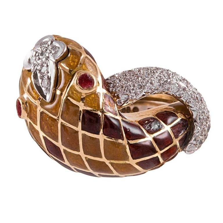 """Rich color hues decorate this lifelike snake ring as its body encircles your finger with a harlequin pattern of enamel and diamonds. Rubies glisten in his eyes and compliment the golden mustard and reddish brown shades of his """"scales"""". The"""