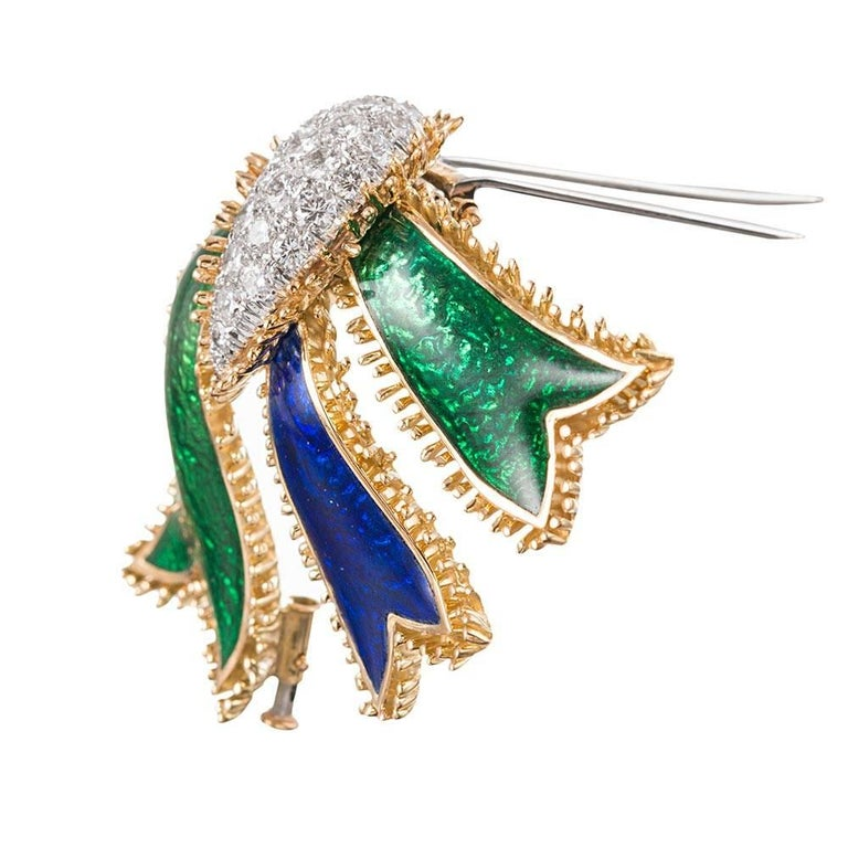 David Webb's iconic creations are hallmarked by striking combinations of enamel and gemstones. This substantial brooch measures 2.5 by 2 inches and offers bold strokes of Kelly green and admiral blue enamel in dramatic contrast to brilliant