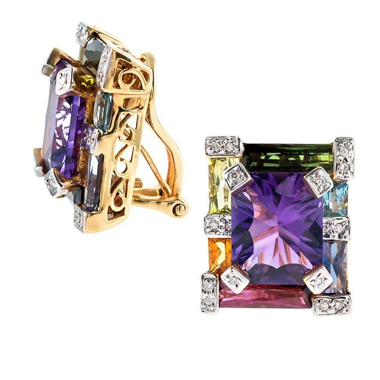 A colorful bounty of assorted gemstones are assembled in symmetrical architecture and mounted in 18k yellow gold. In total, the colored stones weigh 12.10 carats and are accented with .12 carats of white diamonds. Currently clips, a post can be