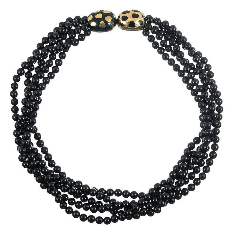 Measuring 17.5 inches in overall length, the necklace is designed as five strands of polished 6mm onyx beads, connected by an opposing pair of 18 karat yellow gold and black enamel ovals. The clasp can be worn off to one side, allowing display of