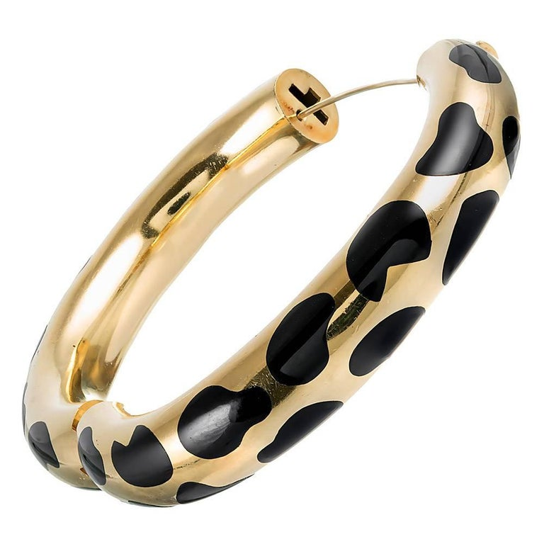 The three-dimensional bangle is rendered in 18 karat yellow gold and spotted with a pattern of black enamel. The interior diameter is 2.25 by just under 2 inches. The piece opens with a single hinge and is secured by an interior concealed safety.