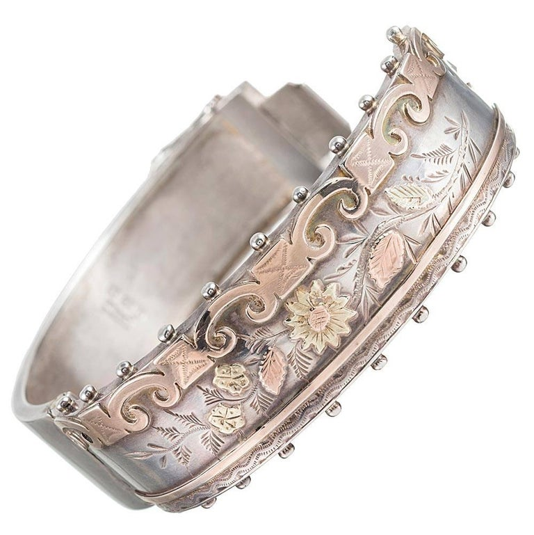 Measuring ¾ of an inch wide and with an interior diameter of 2.25 by 2 inches, this classic Victorian bangle is made of silver and accented with green and rose gold. Note the unique asymmetrical design and beautiful engraving.