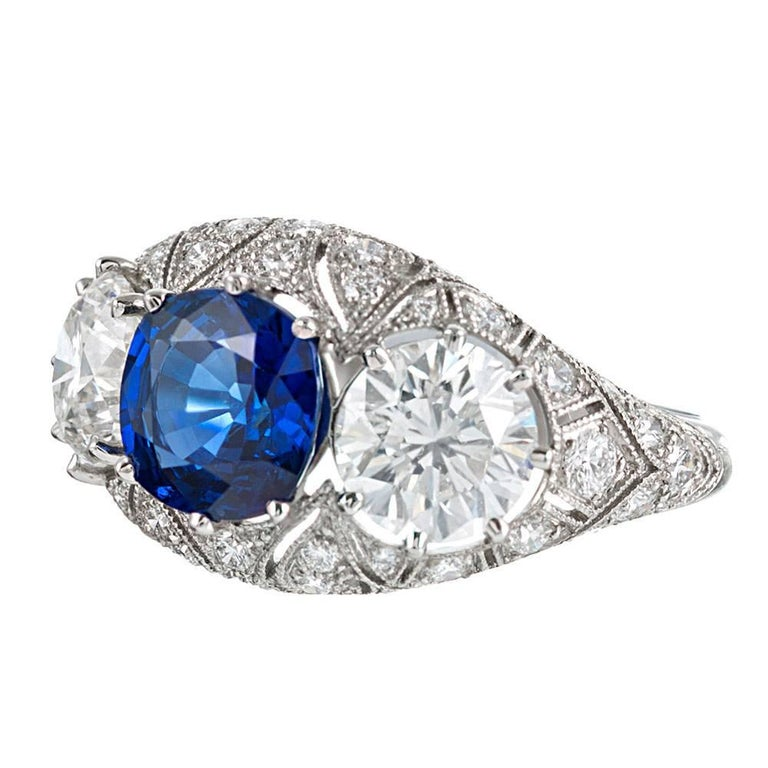 A brilliant combination of art deco inspiration and modern hand-craftsmanship, this platinum mounting is adorned by forty diamonds that weigh .68 carats combined and further accented by scrolling open filigree and mille grain. The center sapphire