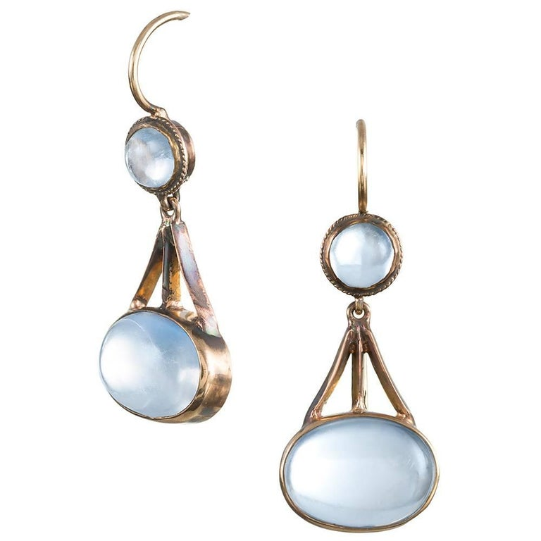"""Early American moonstone earrings created during the """"arts & crafts"""" period, circa 1915. An oval cabochon of blue flash moonstone is suspended from an architectural bridge of 14k yellow gold and topped with a smaller round cabochon. 1.25 inches long."""