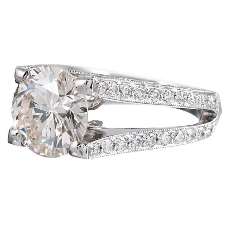An impressive creation with contemporary architecture supporting a 3.90 carat round brilliant solitaire diamond, the ring is rendered in platinum and set with a further 1.96 carats of brilliant diamonds. The major stone is described by the