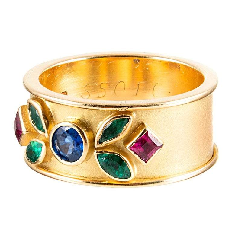 A beautifully-conceived piece, made of 18 karat yellow gold and set with an artful display of colorful gemstones. The substantial body of the band is satin-finished, with high-polished edges and high-polished bezels for the round- marquis- and