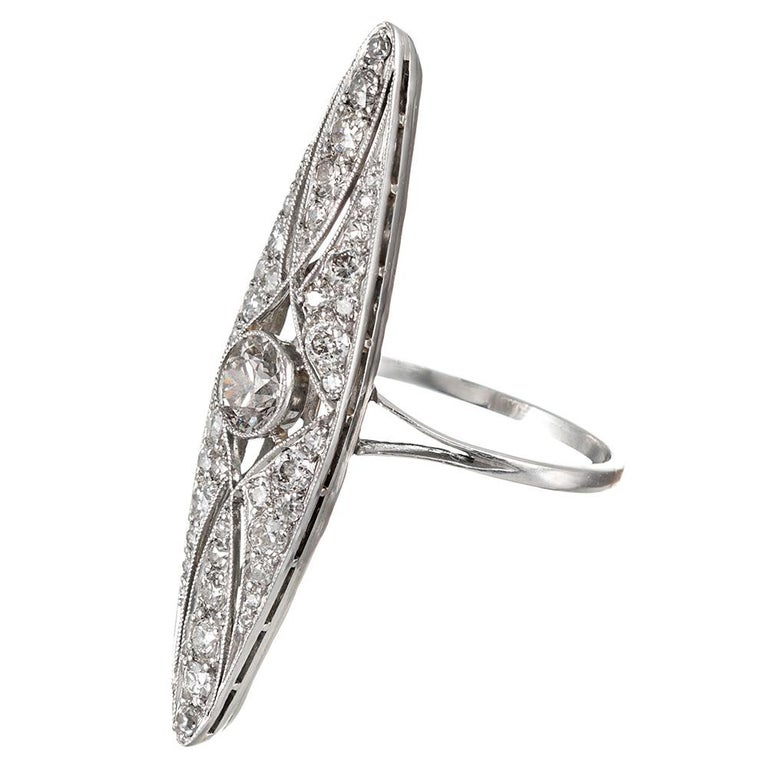 "The elongated and feminine ""navette"" shape looks elegant on the finger, similar to an exaggerated marquis. The design is centered upon a .66 carat old European cut diamond that exhibits K color with Vs2 clarity. A additional .90 carats of old"