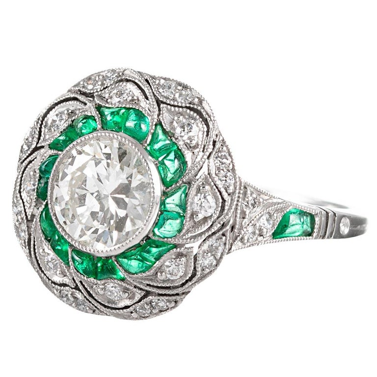 Detail abounds from every angle on this hand made platinum art deco inspired ring. With a .96 carat L/Vs2 diamond set in the center, the impact of the ring is augmented by an additional white diamonds and custom-cut emeralds. Note the filigree under