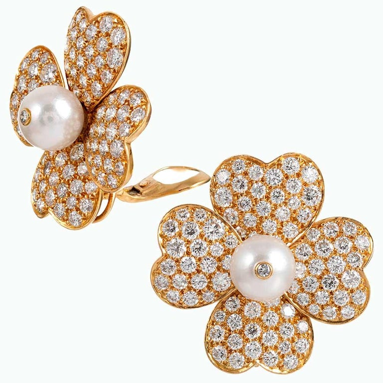 Heart-shaped petals of 18 karat yellow gold are embellished with brilliant white diamonds and fashioned into a flower, it's center punctuated with a lustrous pearl and finished with a diamond solitaire. The esteemed house of Van Cleef & Arpels is