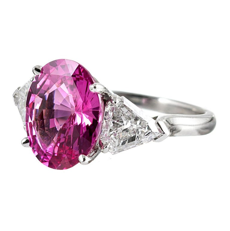 The center pink sapphire exhibits intense, truly gem fine properties, with exceptional color and brilliance. The major stone weighs 5.54 carats. It is flanked by a pair of shield-shaped white diamonds that one must look closely at to appreciate, as