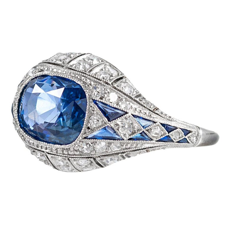 An alluring cornflower blue cushion sapphire sits nestled in an 18 karat white gold bezel, surrounded by an art deco inspired masterpiece of sapphires and brilliant diamonds. The major sapphire is accompanied by an AGL certificate stating the stone