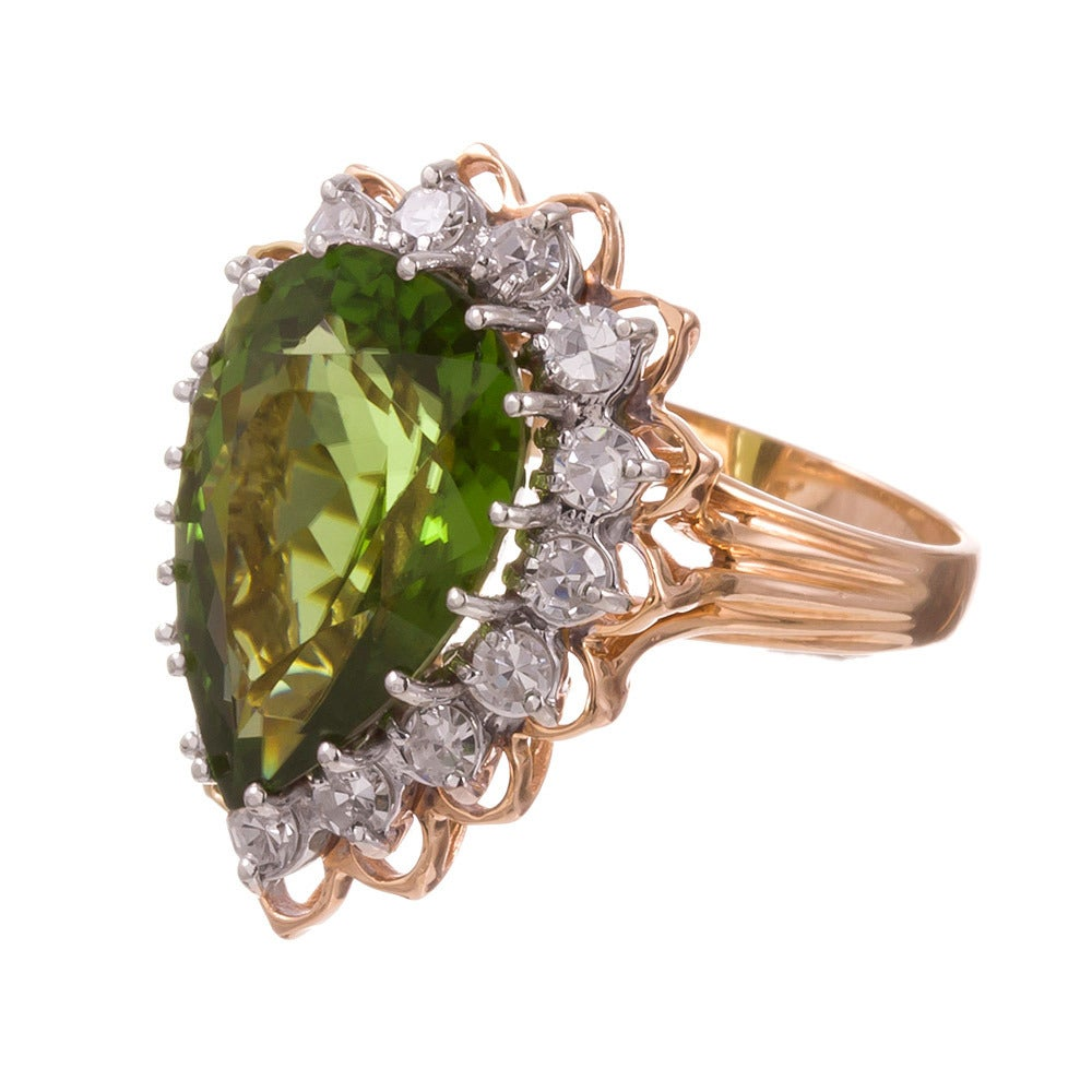 "The ""pear peridot"" ring… say it fast three times! A classic style, with an un-classic center stone. A 9.50 carat pear brilliant peridot, surrounded by .50 carats of brilliant round diamonds, set in 14k yellow and a hint of white gold. Despite its"
