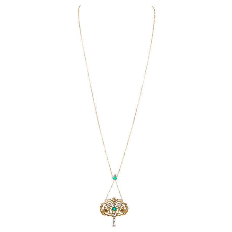 Hand made of 18k yellow gold, with white diamonds set in platinum. The necklace contains a .92- and a .56 carat cabochon emerald and a total of .36 carats of old European cut diamonds. The necklace is appropriately punctuated with a pearl. The star