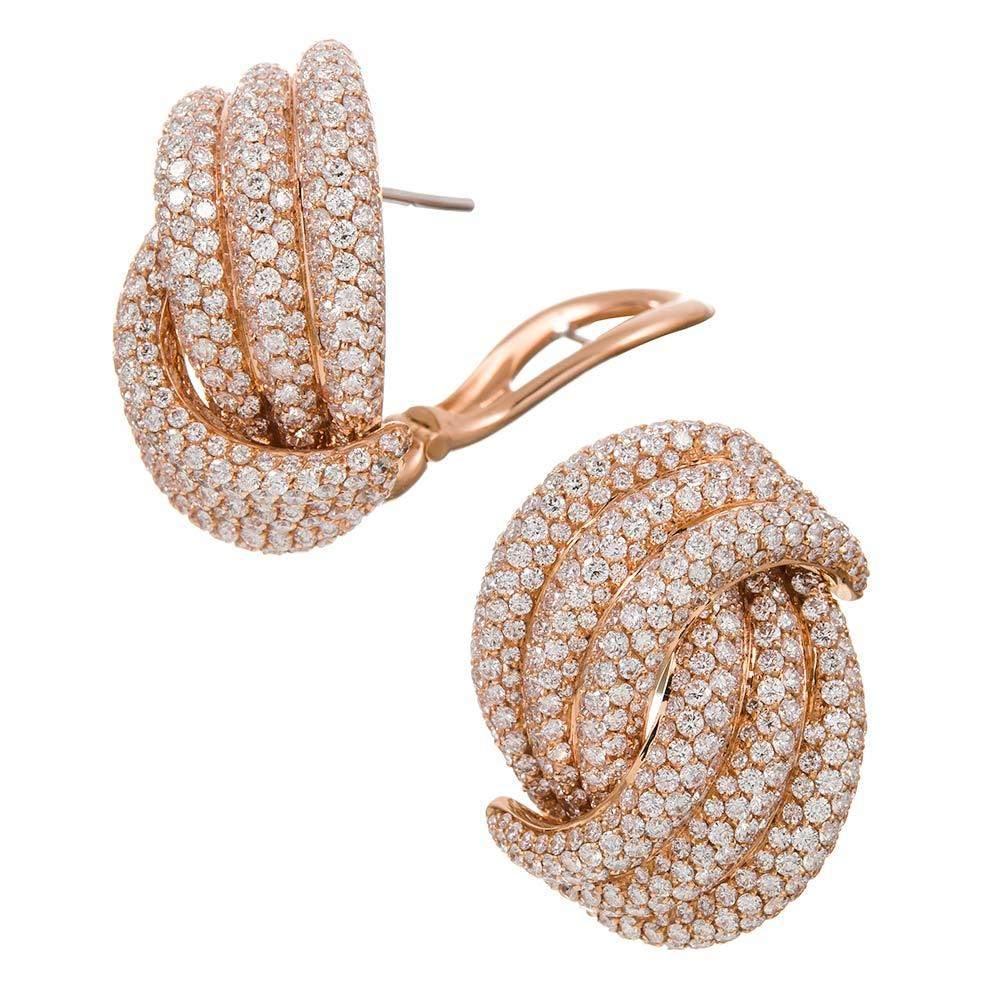 Undulating strands of diamonds form a knot design of brilliant white diamonds, 10.15 carats in total. These earrings are substantial in their design, their materials and their physically size, measuring 1 1/4 by 7/8 of an inch. They are finished