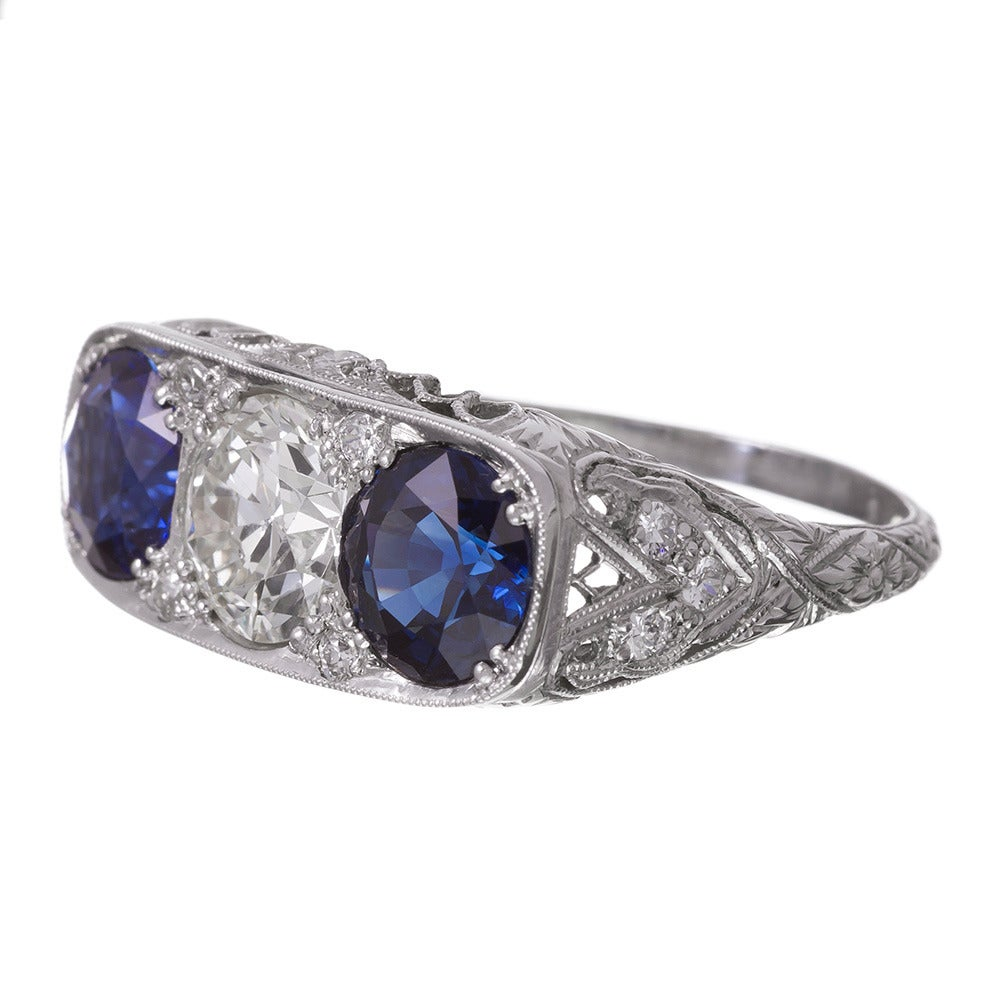 Styled after the classic Victorian English carved ring, but made during the art deco era, this beautifully-preserved three stone ring features a 1.36 carat brilliant round diamond center flanked by an ideally-matched pair of round sapphires that