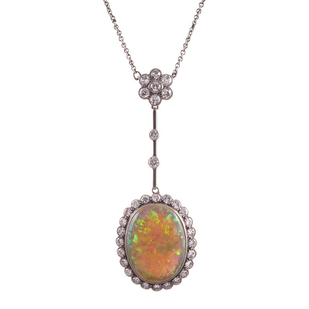 Rendered in platinum over 18k yellow gold, with a 9.5 carat oval opal at the center of a frame of brilliant white diamonds. Each edge finished with milgrain. The design is both sophisticated and playful, with the major pendant swinging suspended