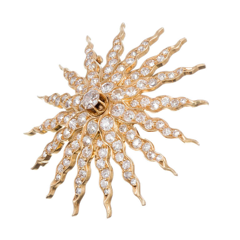 """18k yellow gold starburst brooch, fitted also with a flip-up bale to allow it to be worn as a pendant, and set with 6.50 carats of old European cut diamonds. The layered design of the sun's """"rays"""" are marvelously three-dimensional and add to the"""