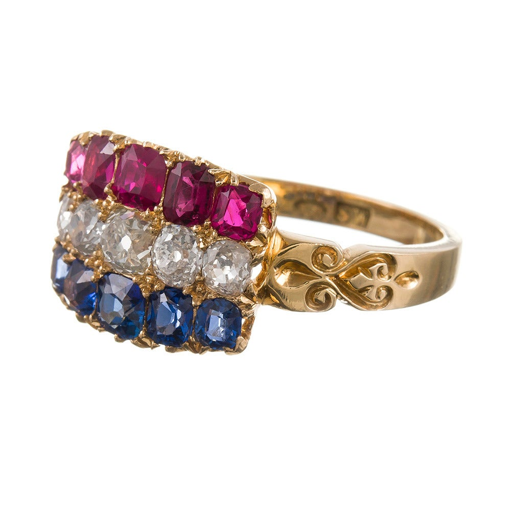A lovely plaque ring with red, white and blue stripes of rubies, diamonds and sapphires, set in 18k yellow gold, a lovely nod to Americana. 1.50 carats each of sapphires and rubies and 1.25 carats of diamonds. Beautiful engraved detail on the sides