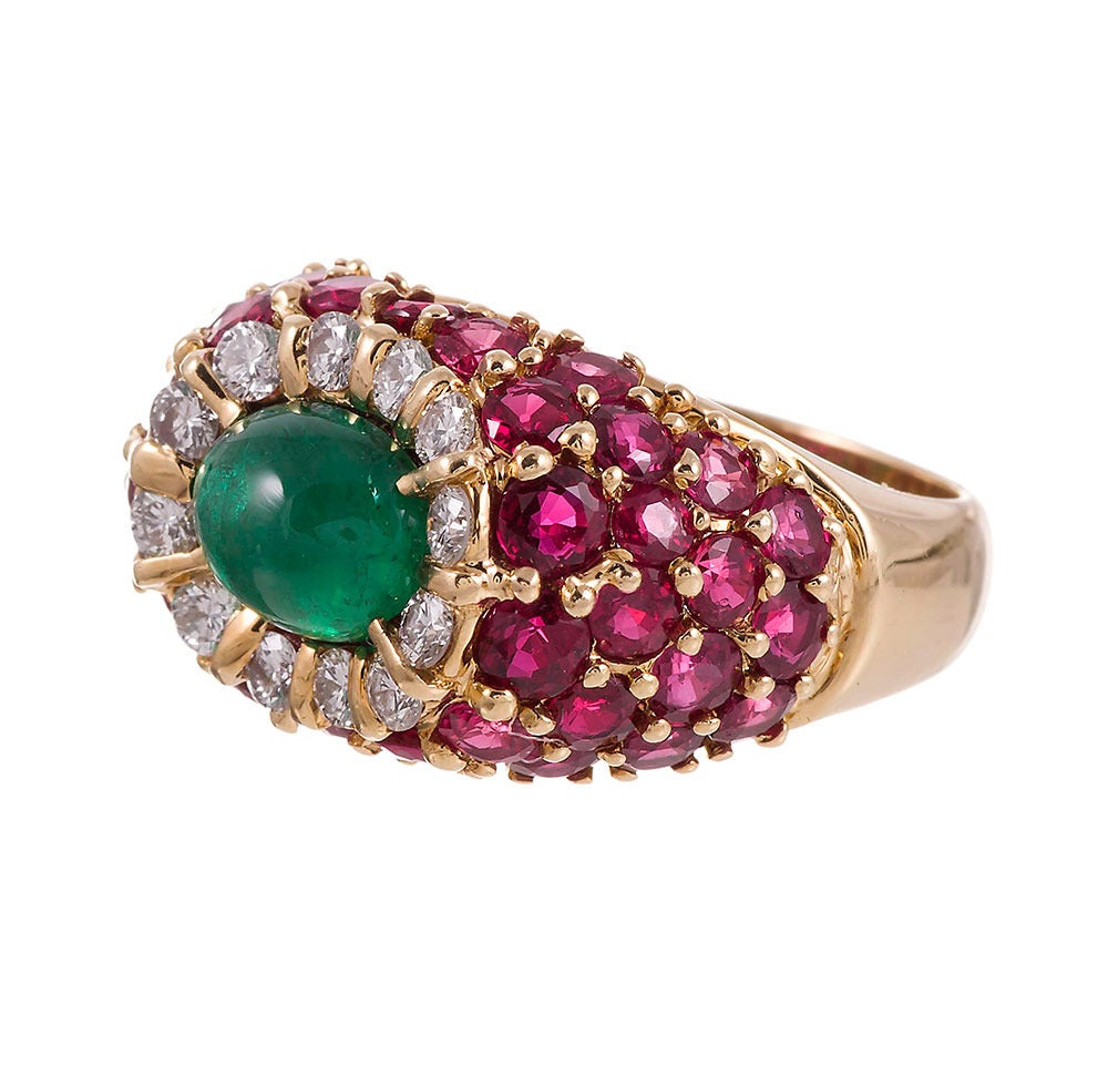 The cabochon emerald sits protected in a nest of rubies, approximately 4 carats in total, and is framed in a border of brilliant round white diamonds, creating a subtle dome shape. A gorgeous color combination assembled with very fine gemstones,