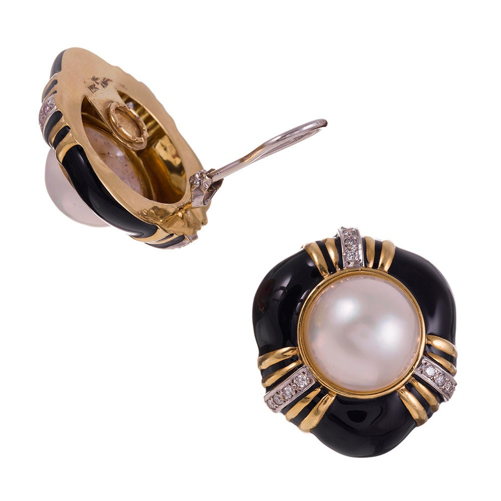 Measuring 1.25 inches in diameter, yet offering a slightly off-round overall shape, the black enamel created a bold backdrop for the substantial mabe pearl center. Strokes of 18k yellow gold are highlighted by parallel lines of diamonds, .48 carats