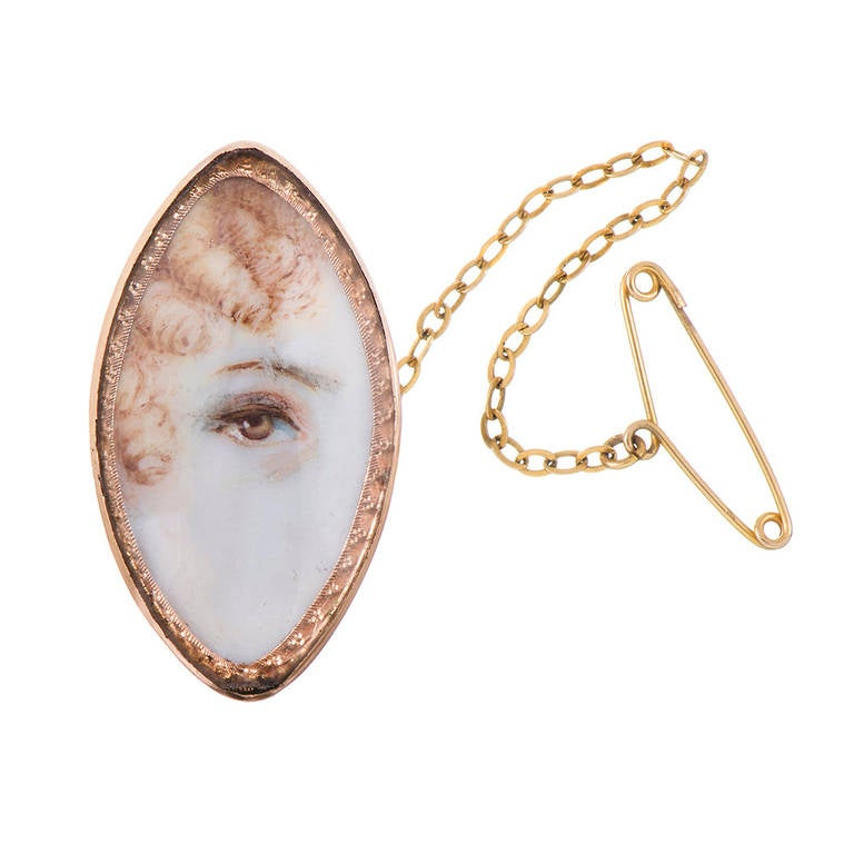 """A marvelous and rare example of the ever-popular lover's eye… this one, with a host of details adding to the charming mystery that surrounds these lovely artifacts. This piece is a unique """"navette"""" marquis shape, in 14k rose gold, depicting a"""