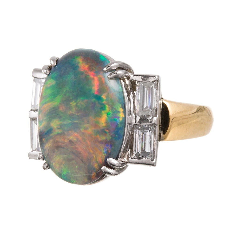 Rendered in 18k yellow gold with a platinum top, this is an unusual and beautiful ring with enough classical style elements to make it timeless, yet plenty of interest to keep it uniquely yours. The black opal center stone weighs approximately 5