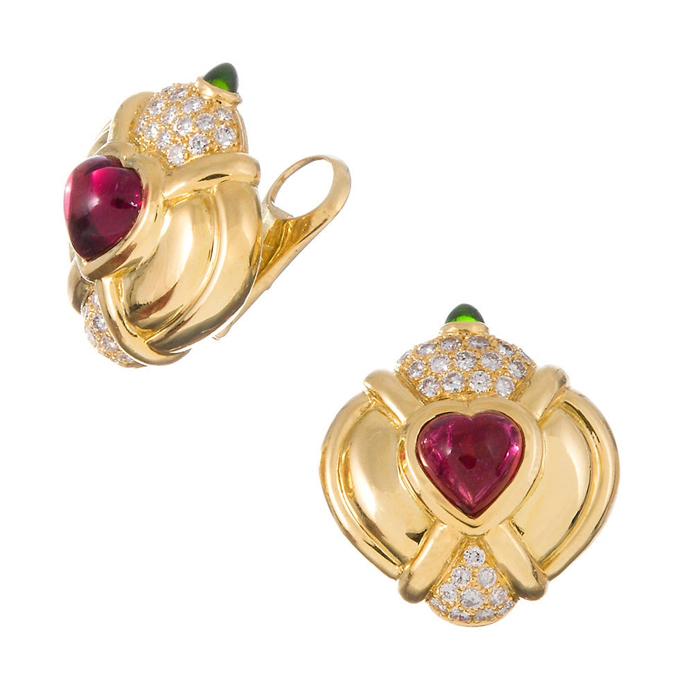 Made of 18k yellow gold, high polished and fashioned into a modified button shape, set with a heart cabochon rubellite, speckled with 2.70 carats of brilliant white diamonds and finished with a cabochon tsavorite garnet. 31 x 28 mm in diameter with