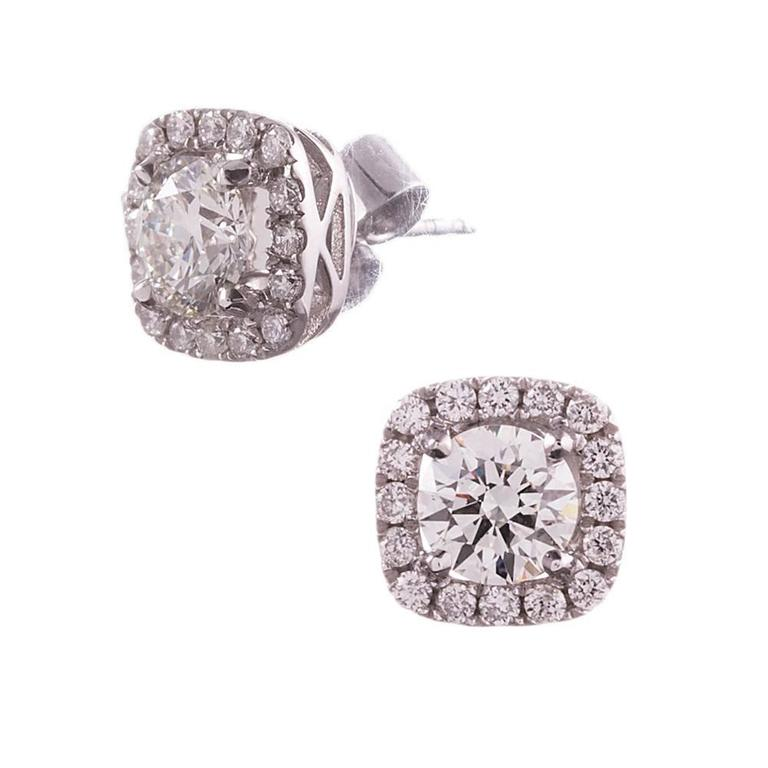 18 karat white gold diamond studs with a cushion shaped diamond halo framing each stone. The center diamonds are GIA graded J color and Si1 clarity, weighing 1.20 carats combined. The thirty-two diamond accent stones weigh .41 carats in total. These