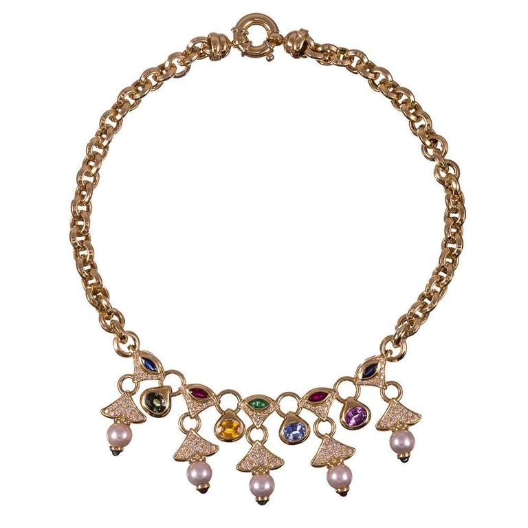 A 16 inch long three-dimensional chain is the backdrop for five fringing drops of diamonds and sapphires, each cascade punctuated by a pearl. This necklace bears striking resemblance Bulgari designs, yet is not signed. The combination of colored