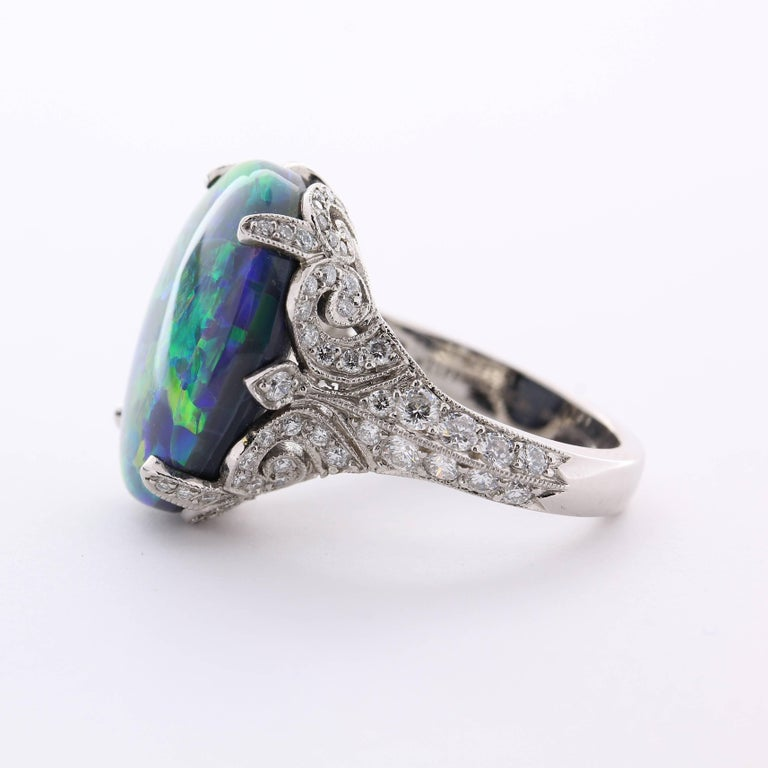 Crafted in platinum, this exceptional Tiffany and Company black opal and diamond ring is a distinctive heirloom-quality piece.    The rich play of color in this flash black opal gives it an unsurpassed splendor and mystique.  Opal is one of the most