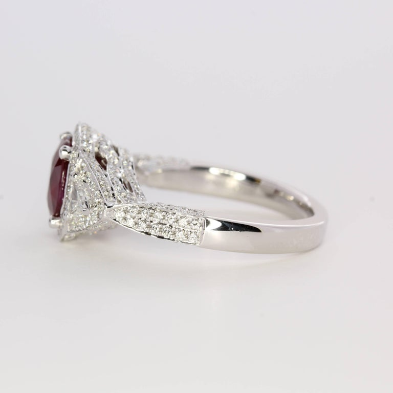 Handcrafted in precious platinum, this natural ruby displays a stunning pigeon's blood, vivid red hue. A cushion-cut at 2.03 carats, the center gemstone is a beautiful display of Mother Nature at her best. Originating in Myanmar/Burma, the ruby is